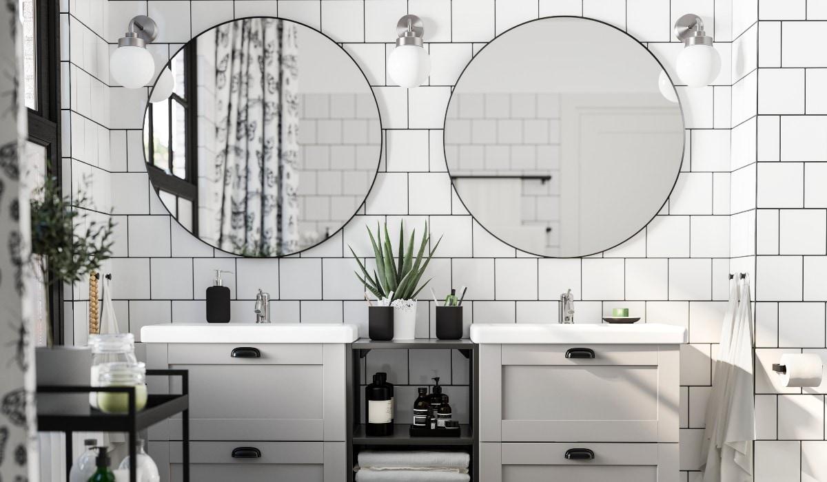 Bagno con mobiletto lavabo bianco con due cassetti e piano grigio, due lavabi bianchi e specchi.