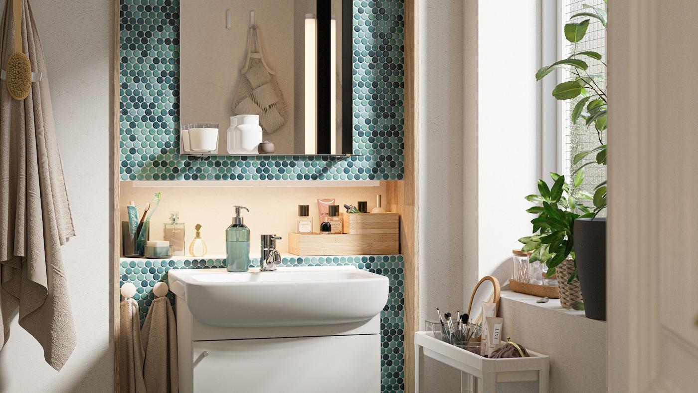 Bagno con piastrelle verdi con mobile per lavabo bianco, specchio con mensola e carrello bianco con prodotti da toeletta.