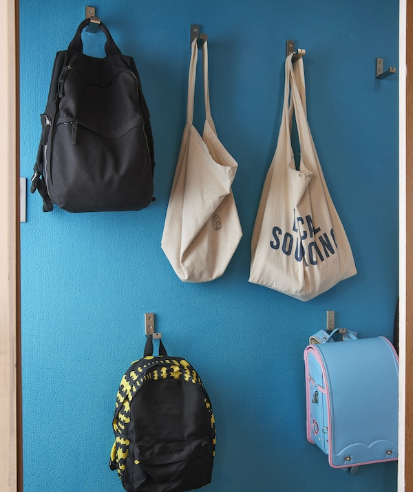 Bags and backpacks hang on hooks at different heights on a blue wall.