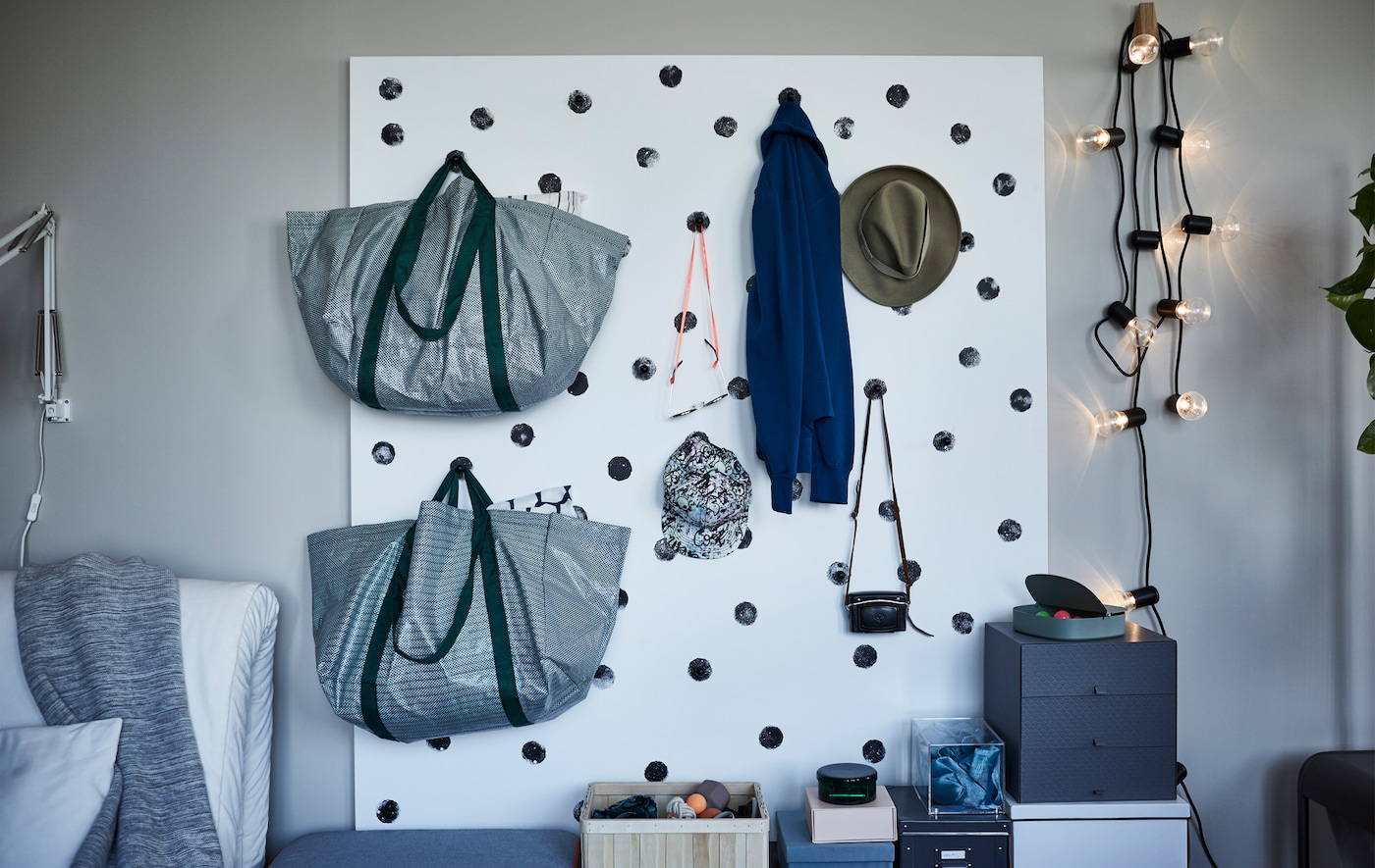 Bags and hats hanging on a white wall storage with black dots, made of a painted plywood sheet and kitchen knobs.