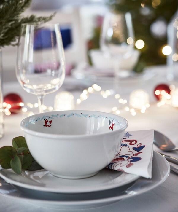 Bahagian meja majlis perayaan yang disediakan untuk satu orang. Berbilang pinggan, rantaian lampu di atas meja, hiasan daun tumbuhan gaulteria, gelas wain.