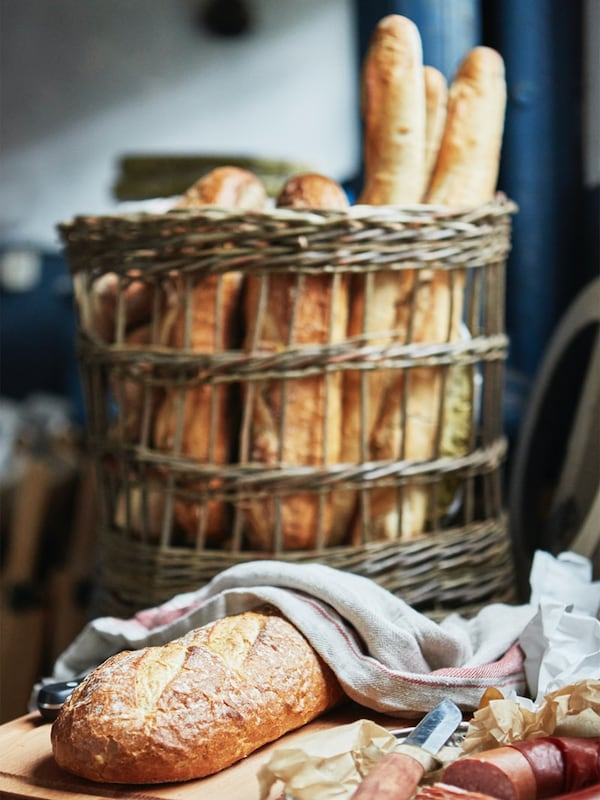 Baked bread and baguettes sit in a weaved basket in the background. A loaf of bread is laid flat on a wooden chopping block, partially covere by a gray cloth in the foreground.