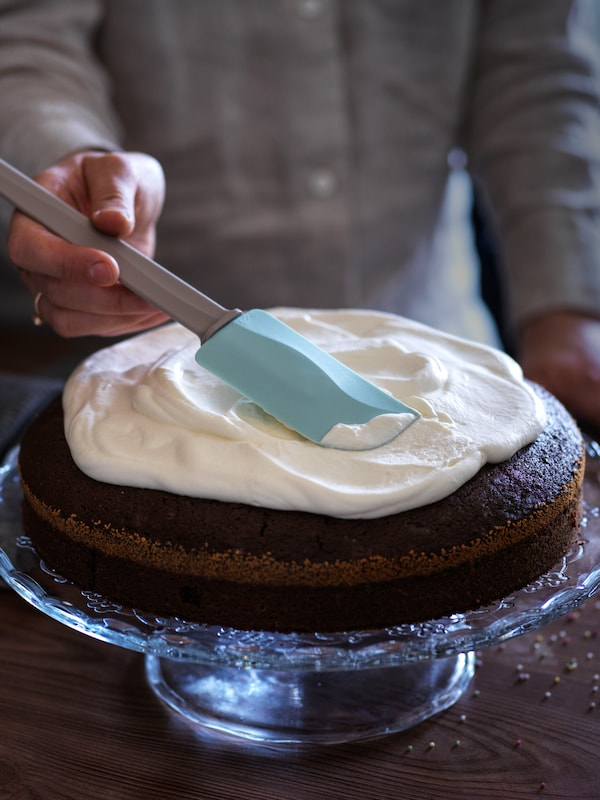 Baker uses IKEA BAKGLAD blue rubber spatula to frost a cake on ARV BRÖLLOP glass cake stand.
