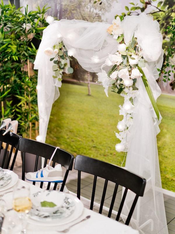 Bakom brudparets stolar vid honörsbordet står en brudbåge skapad av en klädställning och tyll.