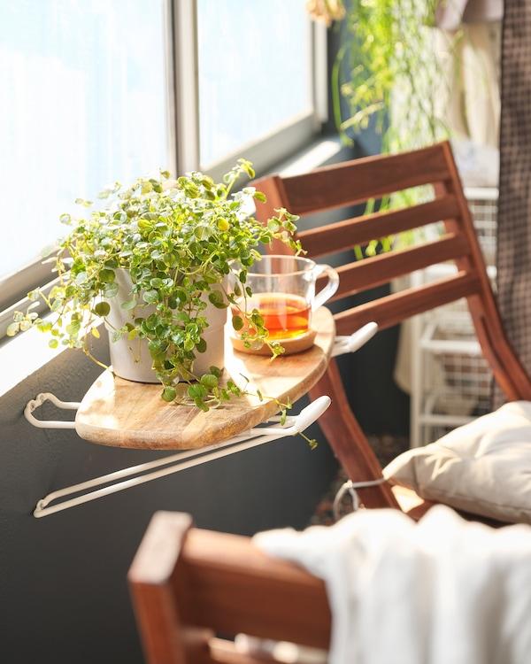 Balcon cu bufet micuț creat dintr-un tocător așezat pe cârlige SKRÄLL, pe care sunt așezate ceai și o plantă, cu scaune alături.