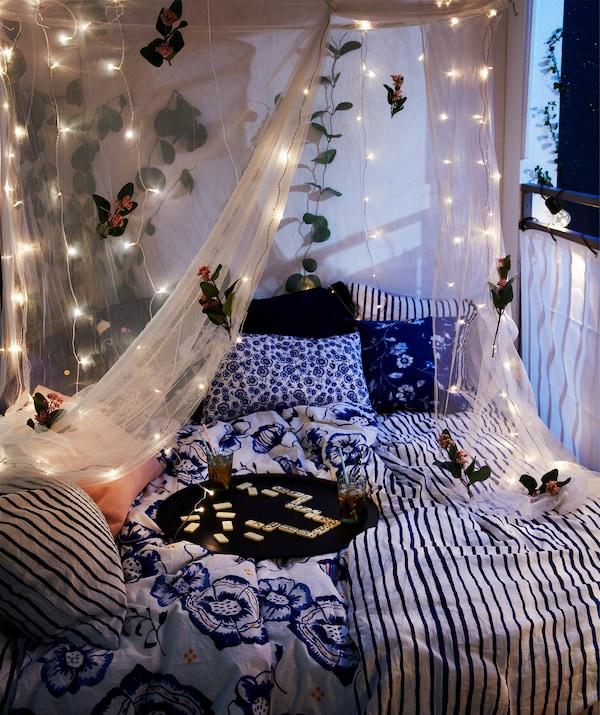 Balcon la nuit, avec lit double, plateau avec boissons posé dessus et moustiquaire suspendue décorée de guirlandes lumineuses.
