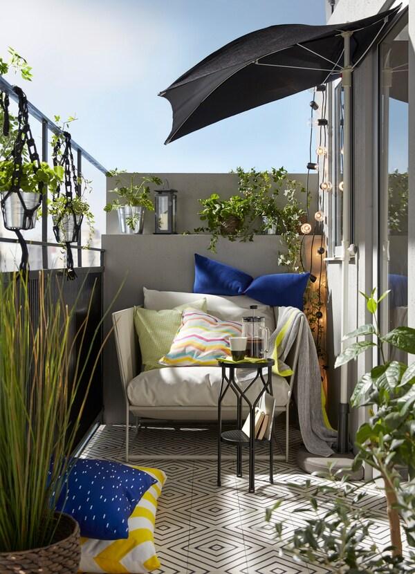 Balcon mic de apartament, cu plante, o umbrelă de soare și un confortabil fotoliu HAVSTEN interior/exterior, bej.