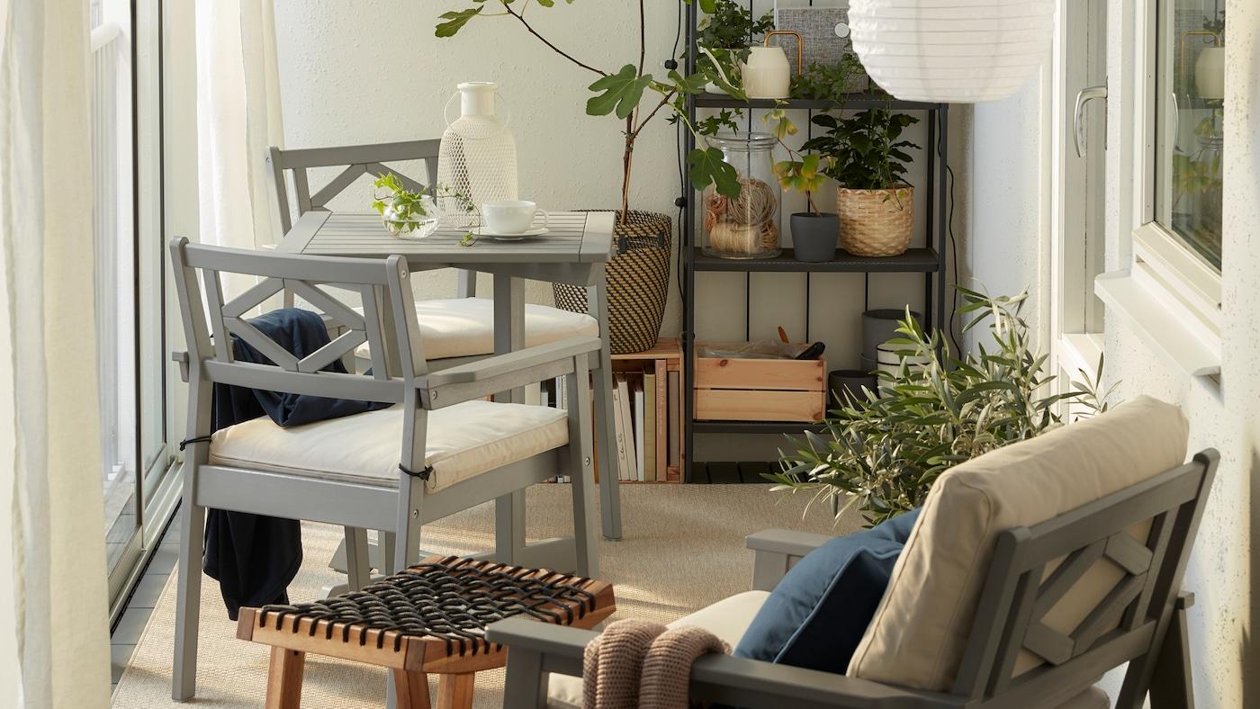 Balcón pechado con mobles BONDHOLMEN en gris, lámpadas de teito redondas, unha alfombra beixe, cortinas brancas e moitas plantas.