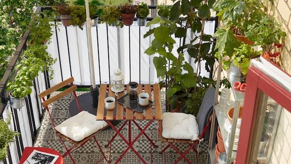 Balcón pequeño con muchas hierbas y plantas, un estante con macetas, una base para sombrilla, dos sillas y una mesa.