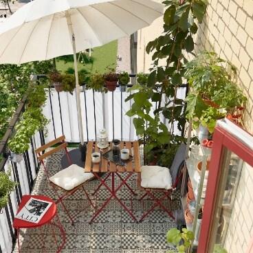 Balcón pequeño con muchas hierbas y plantas, un taburete rojo, un parasol blanco y dos sillas y una mesa plegables.