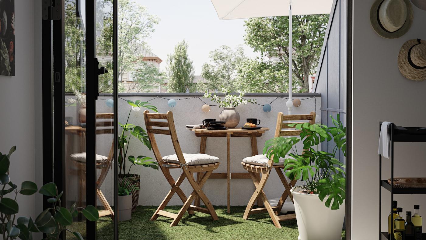 Balcón pequeno cunha mesa e cadeiras de madeira, chan de herba artificial e unha planta Monstera nun testo branco.