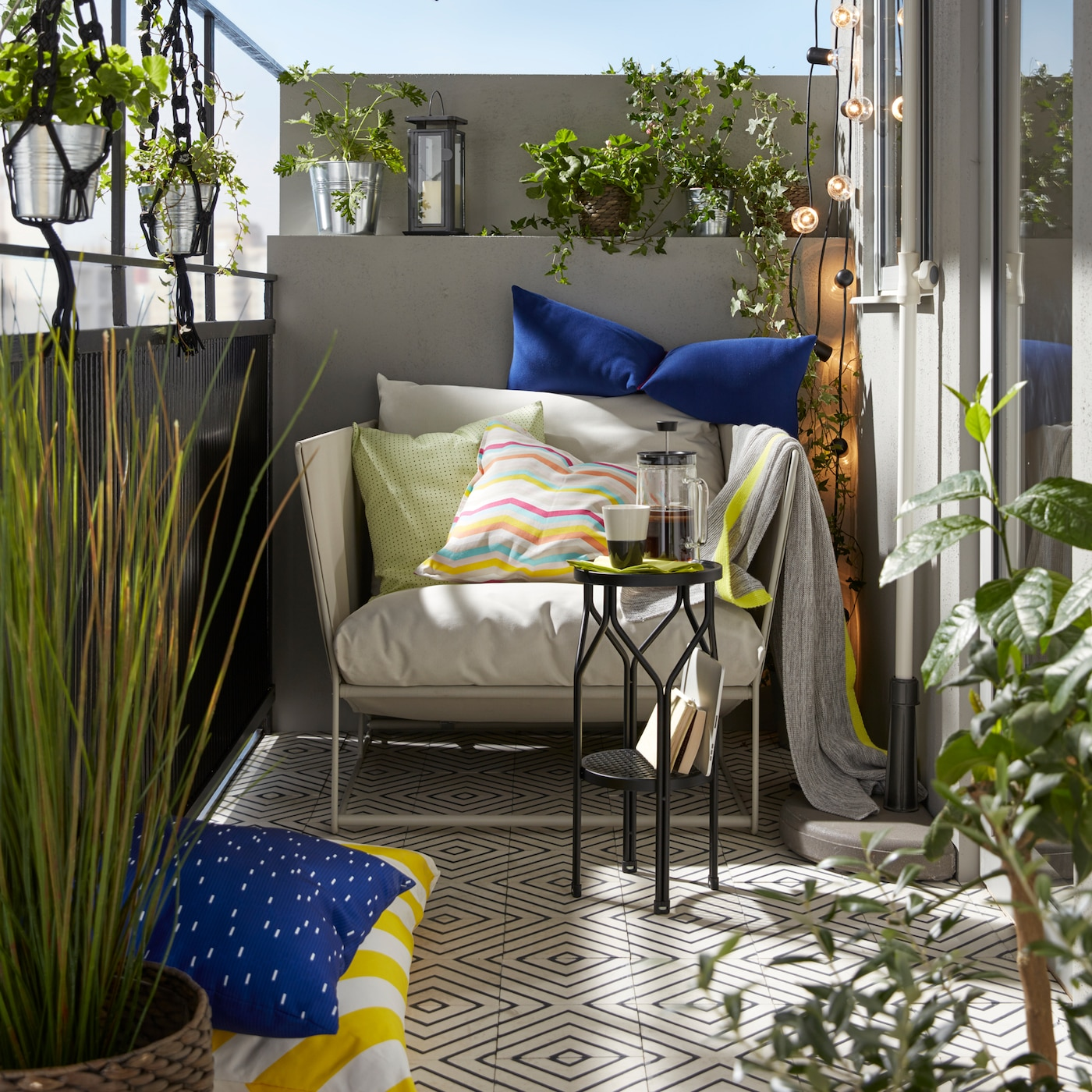 Balcony scene with HAVSTEN in/outdoor sofa and lots of cushions, surrounded by plants.