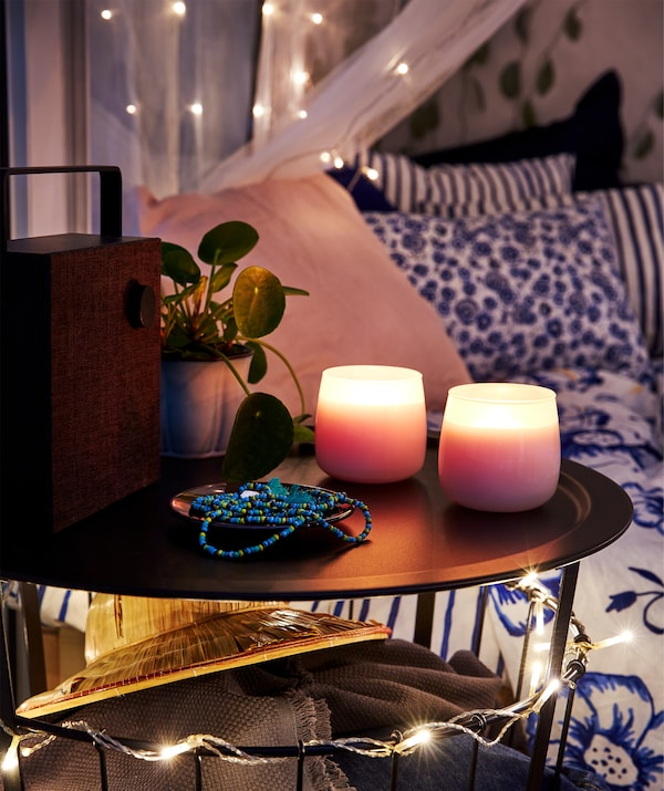 Balcony with bed in the background, fronted by a small round table with an ENEBY bluetooth speaker and lit scented candles.
