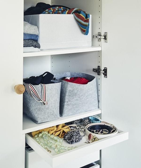 Baldas de armario con cestas, cajas y prendas dobladas, más un cajón de accesorios.