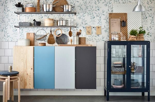 Baldas GRUNDTAL, armarios de pared cerrados y un armario FABRIKÖR con puerta de cristal organizando el equipo de cocina compartido.
