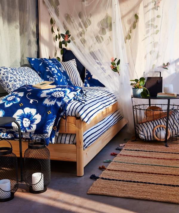 Balkón s dvomi posteľami UTÅKER, ktoré sú uložené na sebe do tvaru pohovky s vankúšmi a prikrývkami.