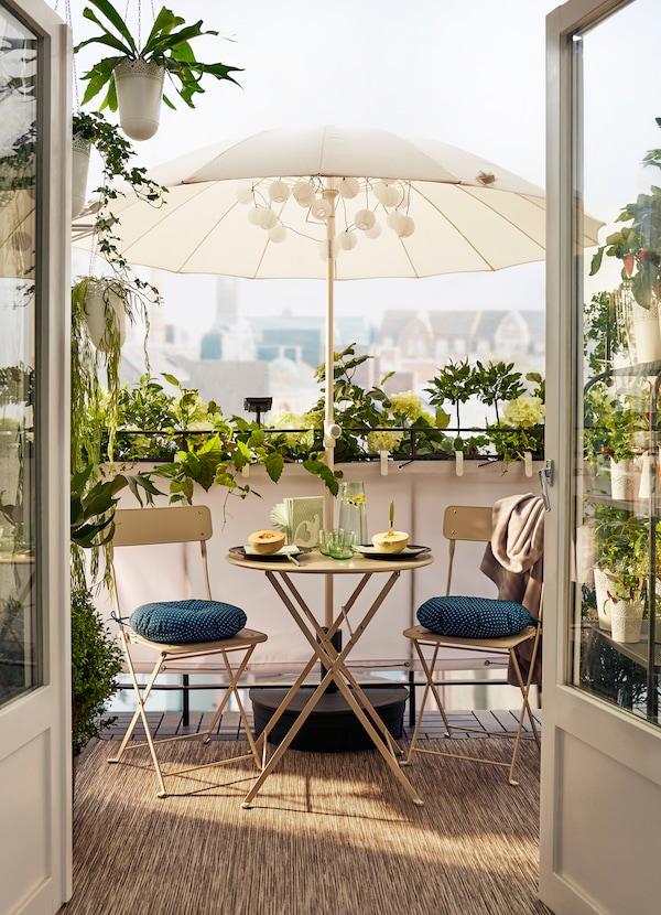 Balkong med beige bord och stolar under ett parasoll, omgivet av växter.
