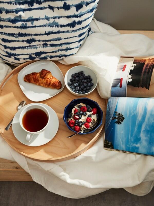 Balkonhoek met een rond dienblad op beddengoed met daarop een STRIMMIG kom met havermout uit de koelkast en bessen, en een kop thee.