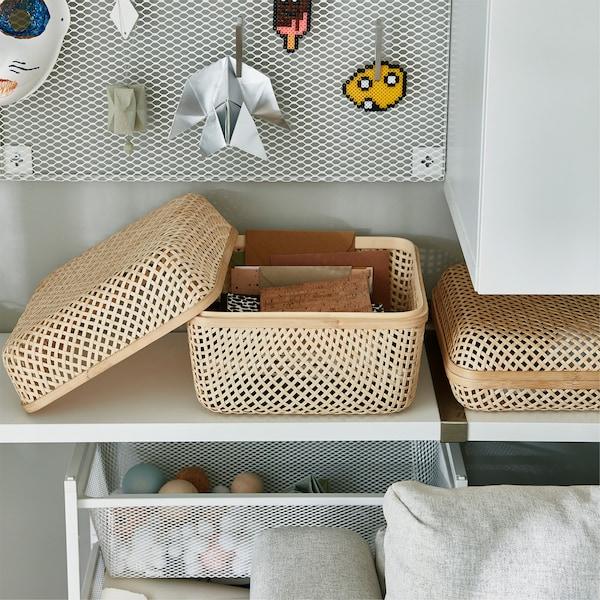 Bambusowe, siateczkowe pudełko SMARRA stojące na półce. Pudełko jest otwarte i widać w środku zeszyty.