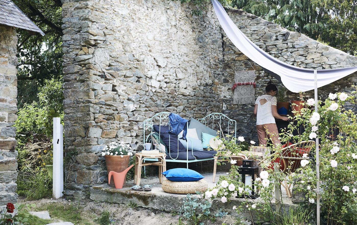 Banc, chaises et tables d'appoint garnis de coussins colorés dans un coin du jardin entouré de murs.
