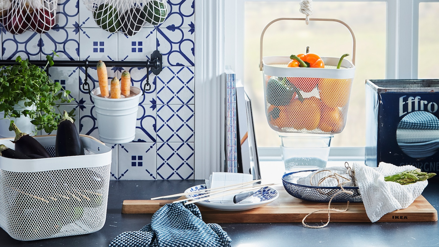 Bancada de cozinha com produtos em diversos cestos, alguns suspensos, como sacos de rede KUNGSFORS e cestos RISATORP.