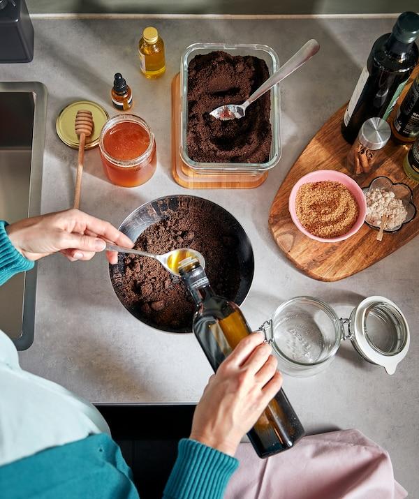 Bancada de cozinha com uma pessoa a preparar uma mistura, vertendo óleo em cima de uma taça com borras de café. Recipiente com tampa KORKEN vazio ao lado.