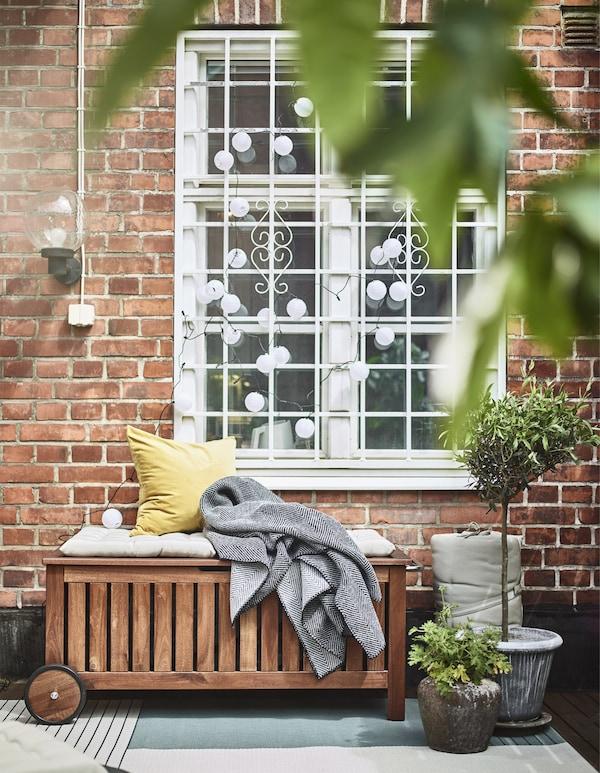 Banco ÄPPLARÖ/TOSTERÖ con bolsa de almacenaje de IKEA con algunos cojines y una colcha, y plantas en macetas en el exterior de una ventana.