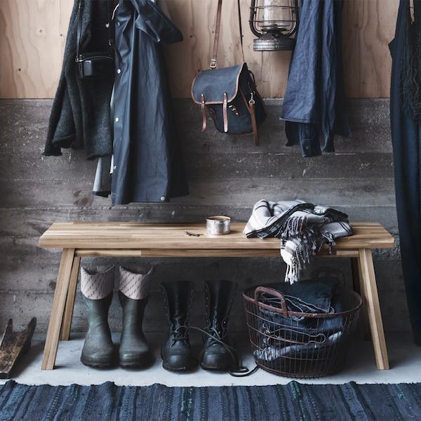 Banco SKOGSTA en un recibidor. Debajo del banco hay varias botas y una cesta y, sobre él, algunas chaquetas colgadas.