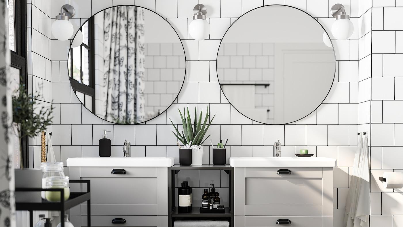 Baño con azulexos brancos, dous espellos redondos, dous lavabos en gris e branco, un carriño negro e tres lámpadas de parede.