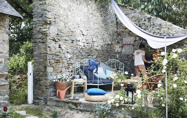 Banquette, chaises, tables d'appoint et coussins colorés sur une terrasse adjacente à un mur de pierre