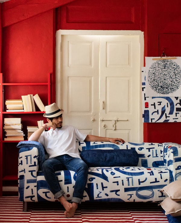 Barefoot man in Panama hat sitting on blue and white sofa in a room with red walls, bookshelf, white door and two-tone rug.