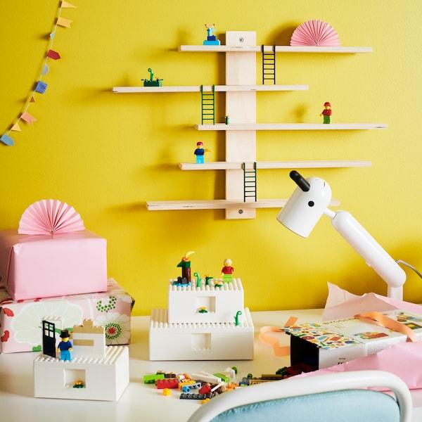 Barevná místnost s krabičkami a kostičkami lega, na stěně je dřevěná police.