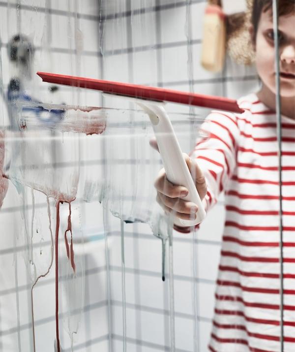 Barn i stribet trøje står i en tør brusekabine og fjerner maling fra en brusevæg af glas med en gummiskraber.