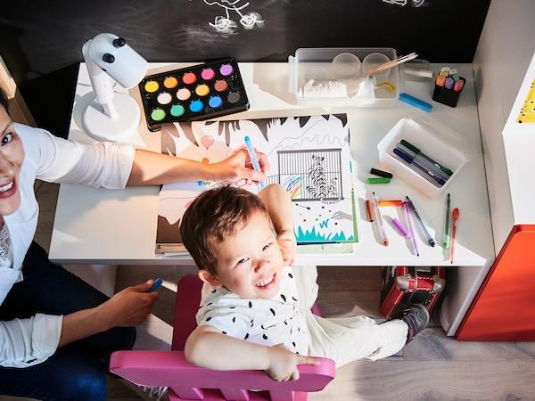 Barn som ser stolt mot kamera mens han stolt viser frem tegning