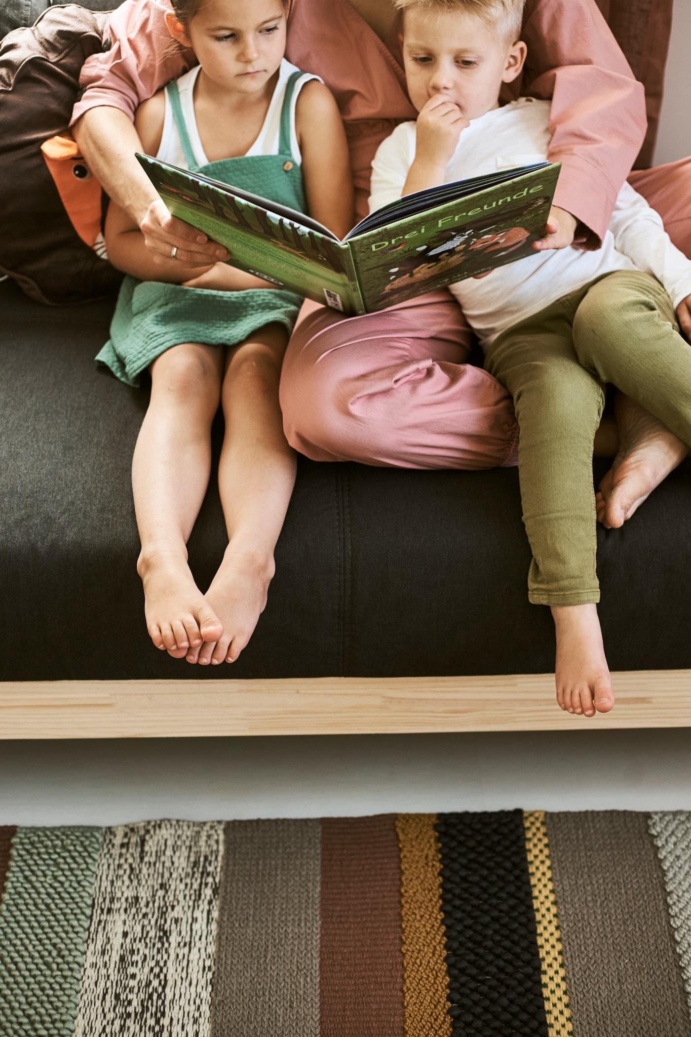 Barn som sitter i säng och läser saga.