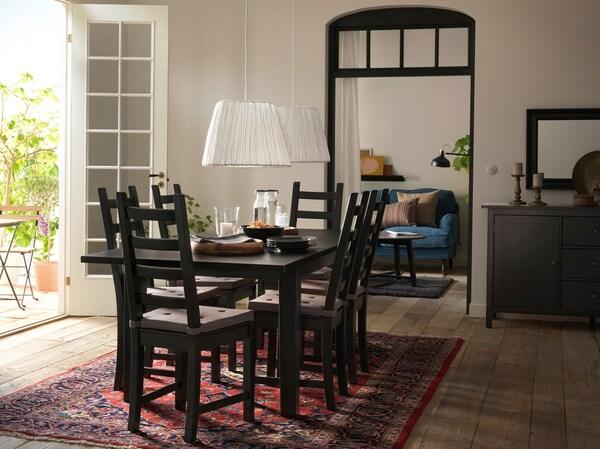 Barna és krémszínű étkező, hagyományos asztallal és székekkel, illetve egy piros perzsaszőnyeg.