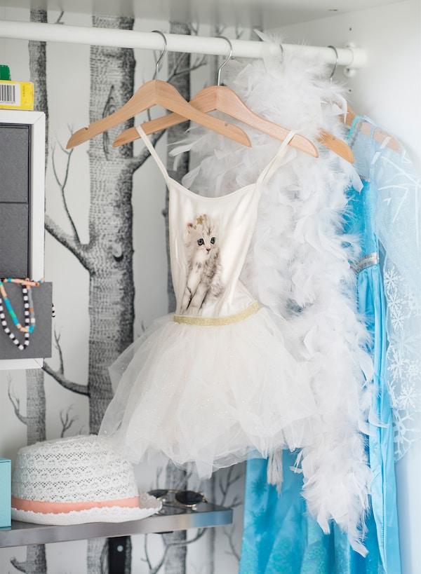 Barra blanca para ropa KOMPLEMENT de IKEA con perchas de las que cuelgan divertidos trajes y accesorios infantiles.