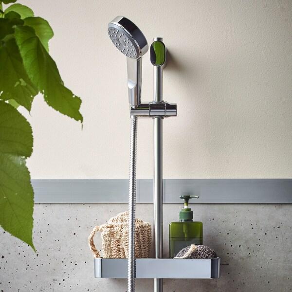Barre BROGRUND chromée avec kit douchette, fixée sur un mur, avec un plateau sur lequel sont posés une éponge et un distributeur de savon.