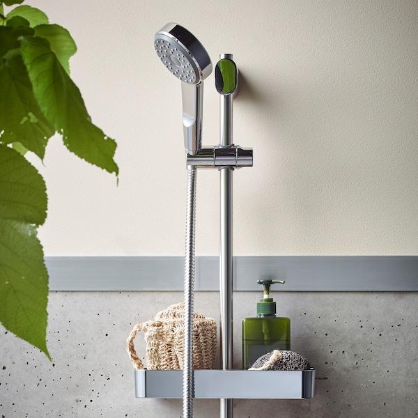 Barre chromée BROGRUND avec douchette/hauteur réglable, fixée sur un mur; avec un plateau accueillant une éponge et un distributeur de savon.