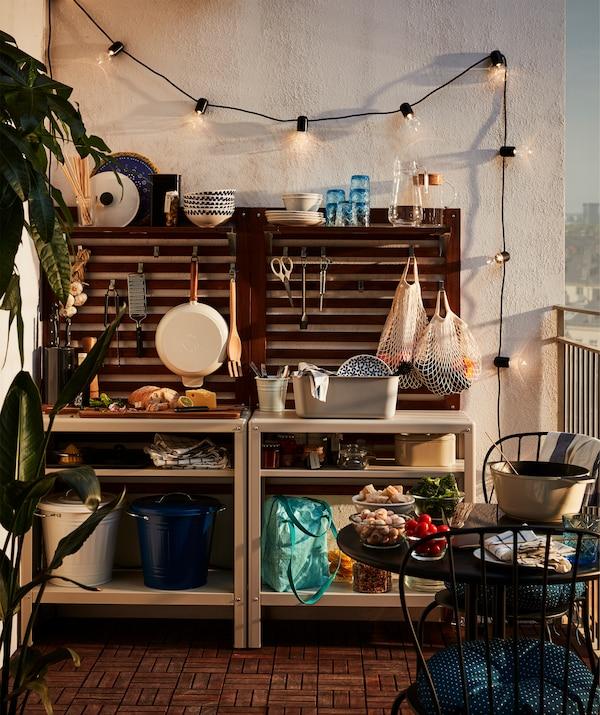 バルコニーの端に設置されたシンプルなアウトドアキッチン。シェルフユニット、ウォールパネル、LEDライトチェーン、キッチン用品が備えられている。