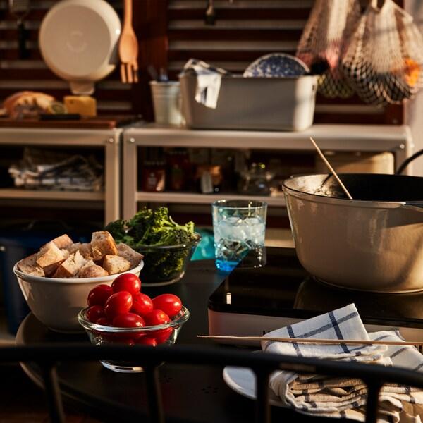 バルコニーの小型の丸テーブルに用意された2人分のフォンデュキット。背景に屋外用キッチンが見える。