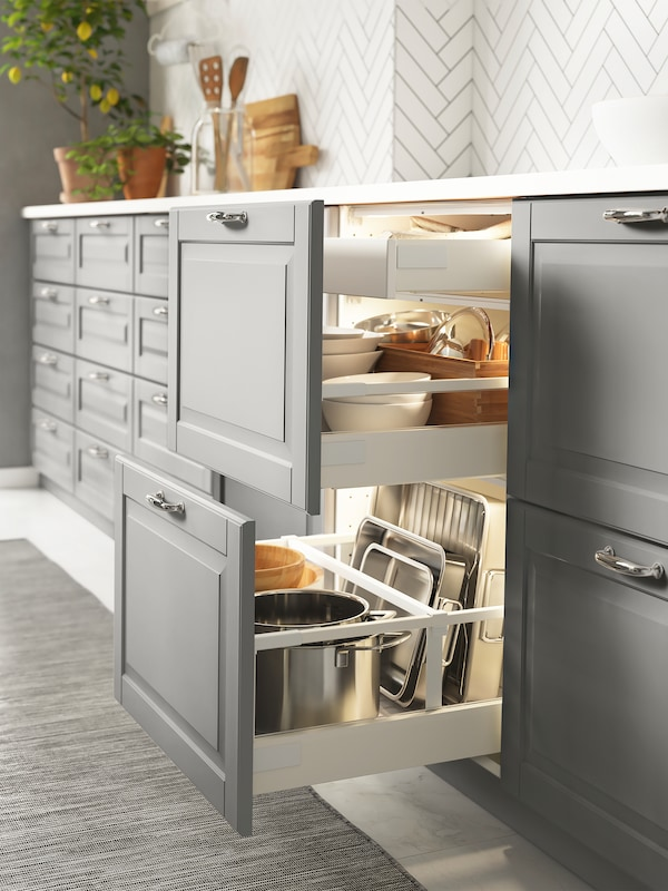 Base cabinets in a kitchen setting with grey drawer fronts, two drawers are open and have cookware and tableware inside.