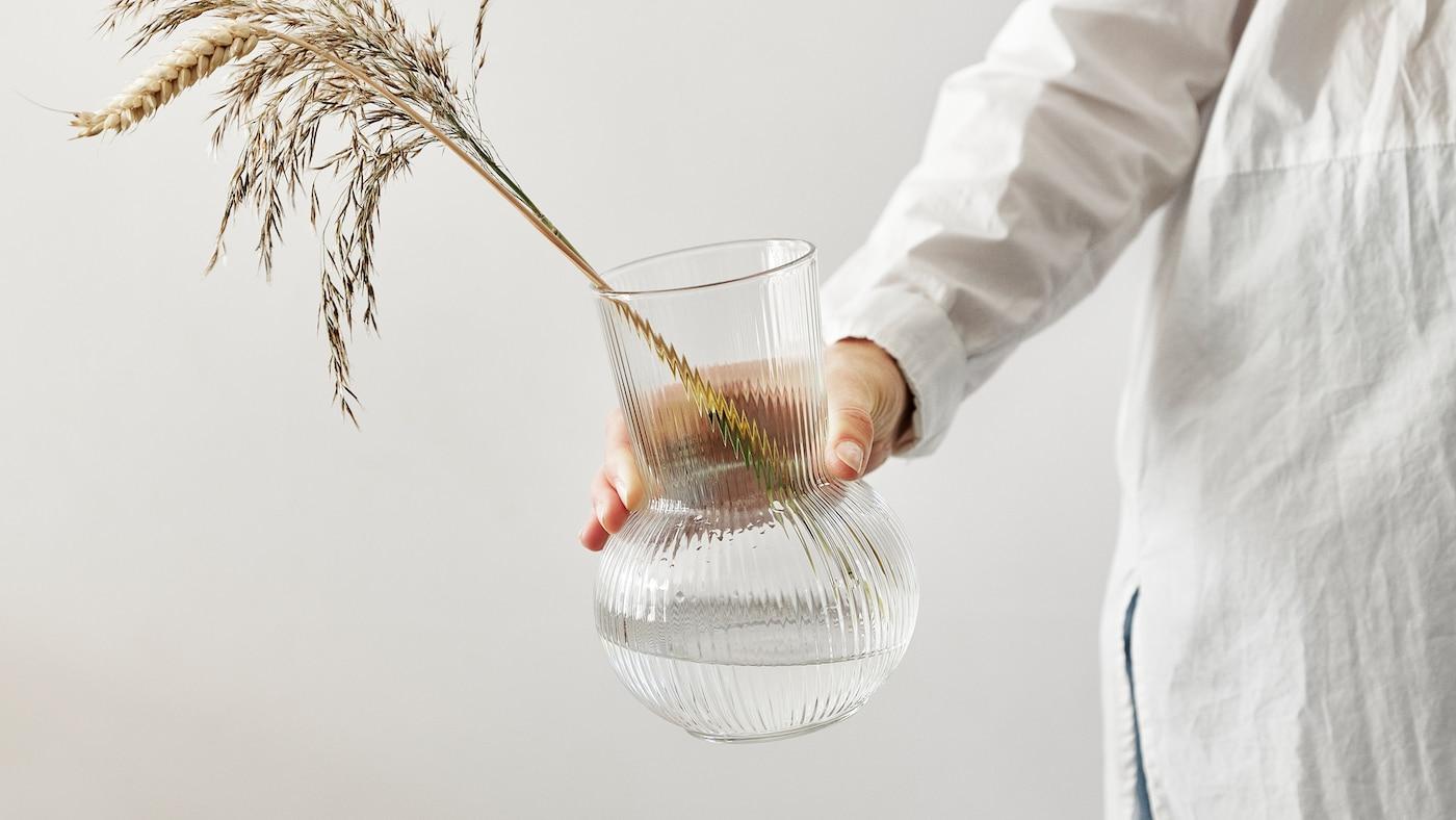 伸ばした手が、クリアガラスのPÅDRAG/ポードラグ 花瓶を持っている。花瓶には小麦と乾燥した草が挿してある。