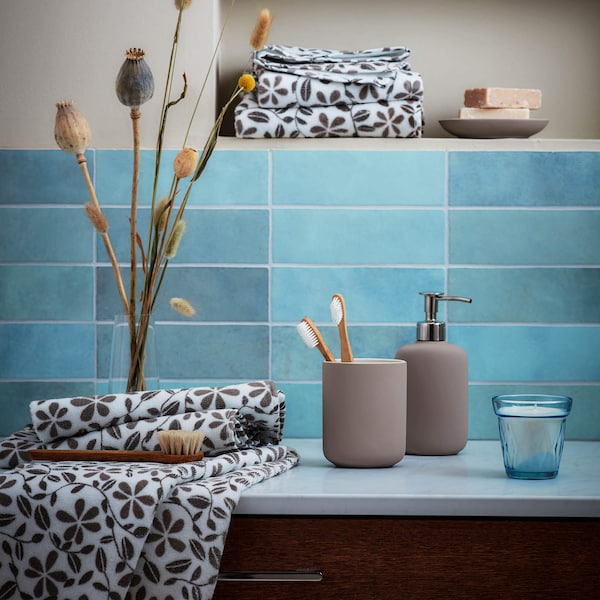 Bathroom sink counter with toothbrushes, towels and soap dispenser