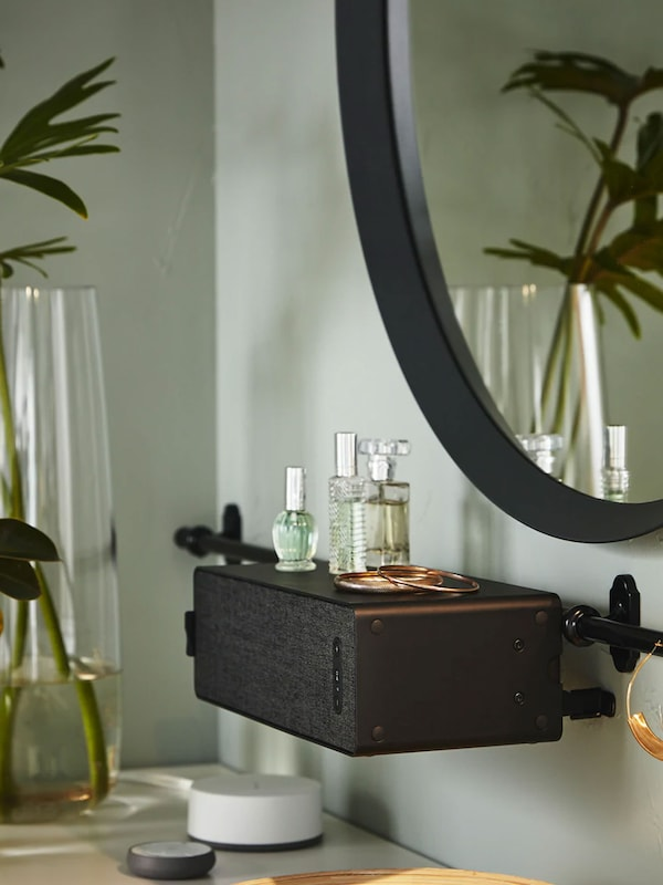 Bathroom vanity with black SYMFONISK speaker attached to wall