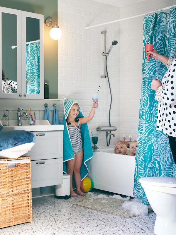 Bathroom with three girls around a bath. One of them, draped in a RÖRANDE hooded towel, makes a play toast with her mother.