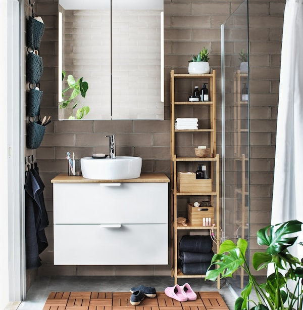 Bathroom with two mirrors, two sink and storage units with diverse toiletry articles plus wall lighting and a large plant.