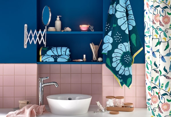 Bathroom with wash basin and colourful, floral-print towels.