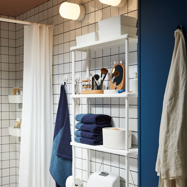Bathroom with white shelves that store blue towels and white storage boxes above a toilet. White shower curtain hangs beside.