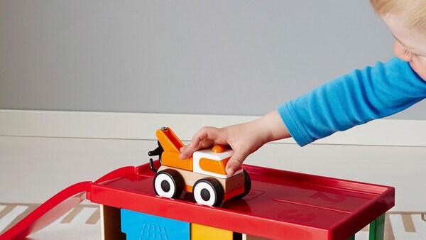 Batole si hraje na podlaze s barevnou hračkou IKEA LILLABO.